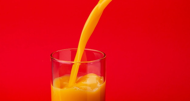 Orange juice pouring into glass, isolated on red background