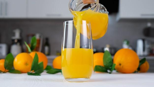 Orange juice pouring into glass on white table in modern kitchen. citrus juice splash