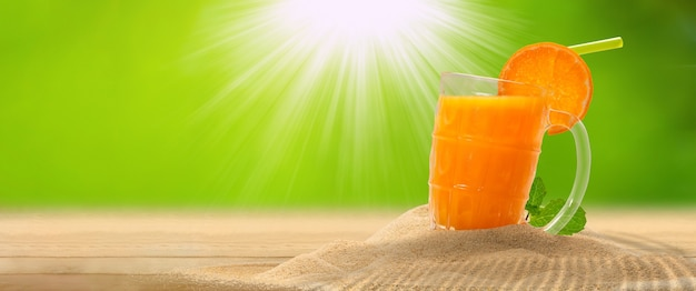 Orange juice on sand with greenery background, copy space