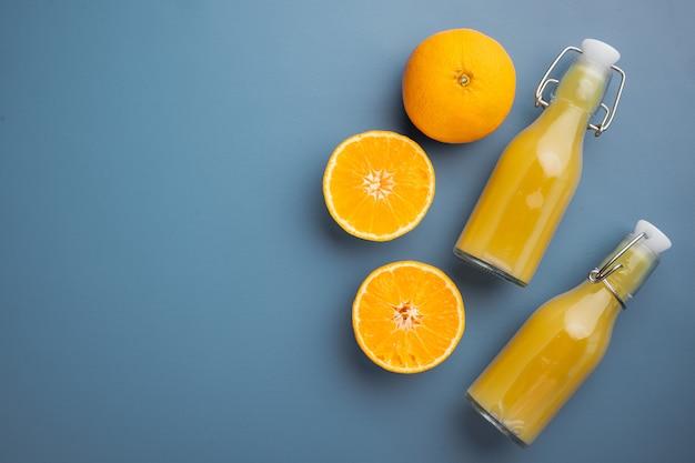 파란색 질감의 여름 배경에 오렌지 주스 세트, 텍스트 복사 공간이 있는 평면도