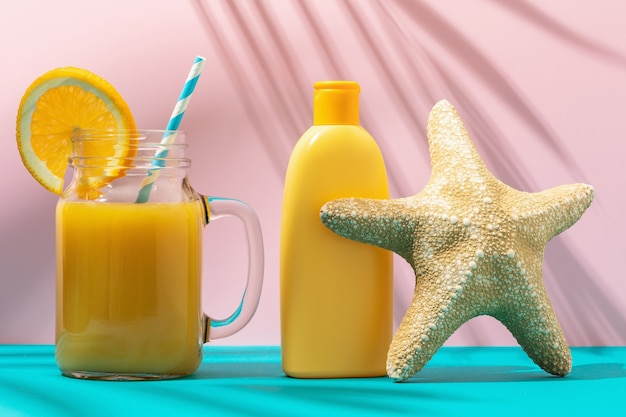 Orange juice starfish and sunscreen on a colored background