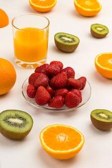 Апельсиновый сок, клубника апельсины киви для здоровой диетической закуски.