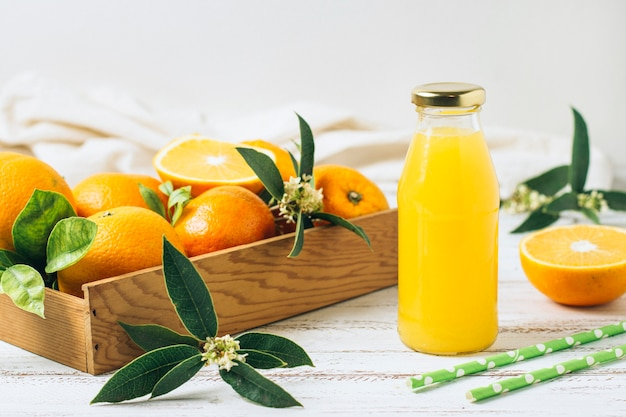 Orange juice next to straws and box full of oranges