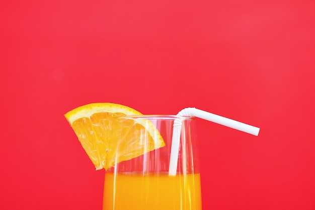 Orange juice summer glass with piece orange fruit on red with copyspace