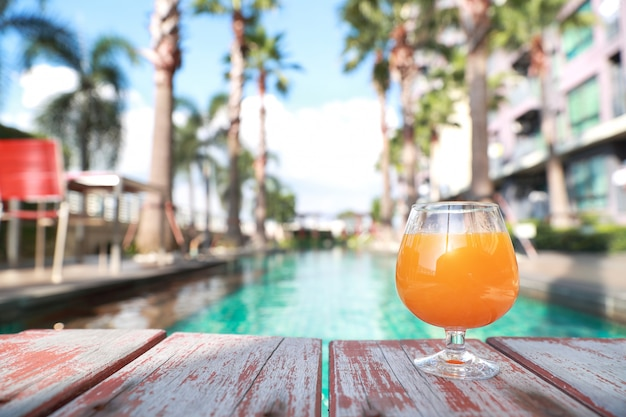 Orange juice on swimming pool with palm tree and copy space