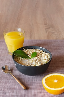 Orange juice with a bowl of oatmeal porridge and a slice of orange