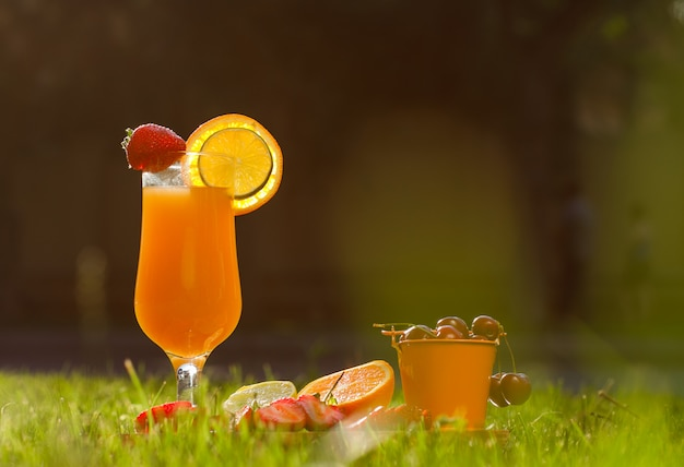 Апельсиновый сок с цитрусовыми, клубника, вишня в бокале на фоне луг, вид сбоку.