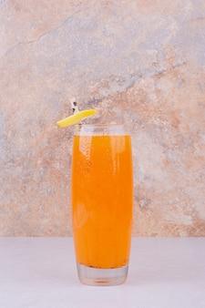 白いテーブルにフルーツスライスとスパイスとオレンジジュース。