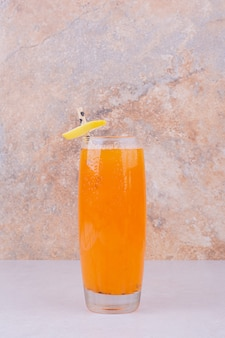 Orange juice with fruit slices and spices on white table.