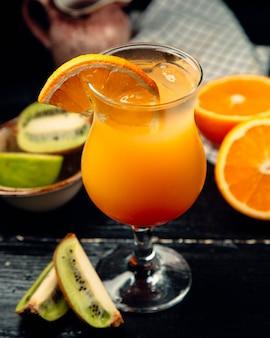 Orange juice with ice cubes and kiwi slices.