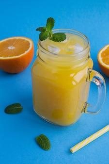 青い背景のガラスに氷とオレンジジュース。クローズアップ。