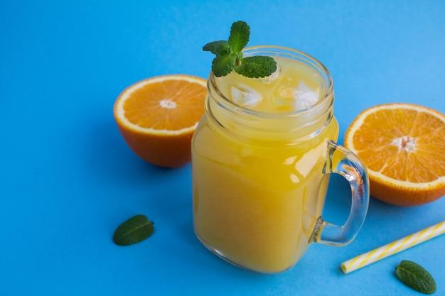 青い背景のガラスに氷とオレンジジュース。コピースペース。
