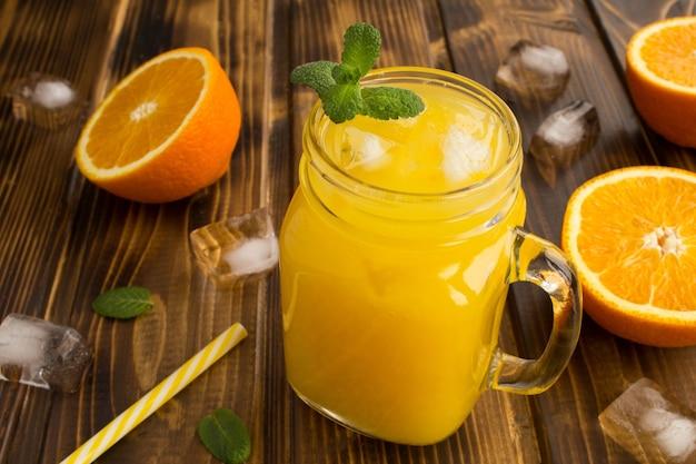 Апельсиновый сок со льдом в стакане на деревянном столе