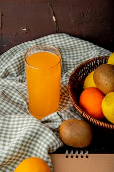 Orange juice with kiwis and other citrus fruits on cloth surface