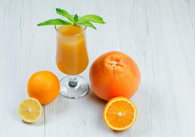 Succo d'arancia con la menta, l'arancia, il limone, il pompelmo in un calice su superficie di legno bianca, vista dell'angolo alto.