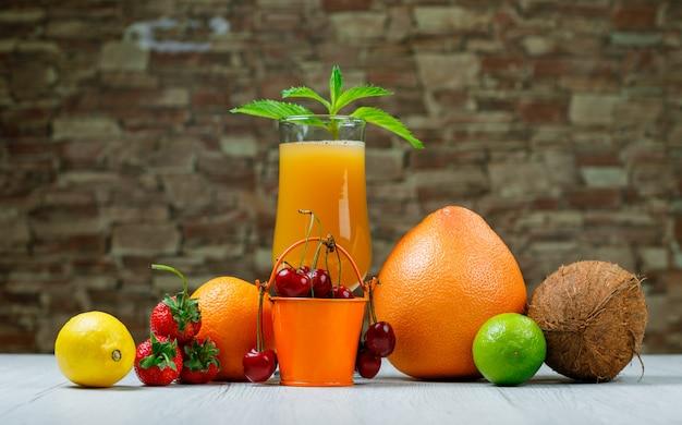 Succo d'arancia con menta, arancia, lime, limone, fragola, ciliegia, cocco, pompelmo in un calice su pietra di mattoni e superficie di legno, vista laterale.