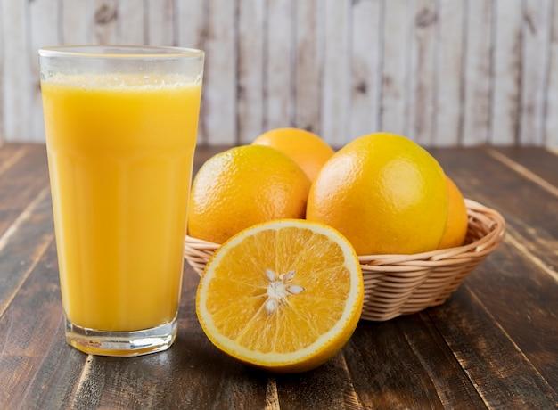 バスケットにオレンジとオレンジジュースを入れ、木製のテーブルにフルーツをカットします。