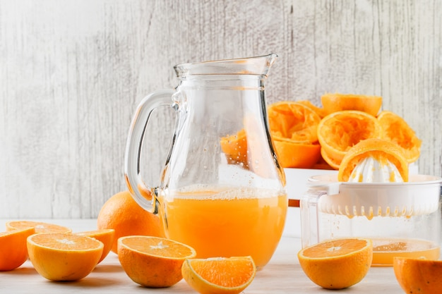 Orange juice with oranges, squeezer in a jug on white surface