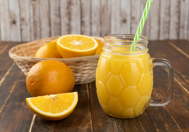 木製のテーブルの上にスライスしたオレンジとオレンジジュース。