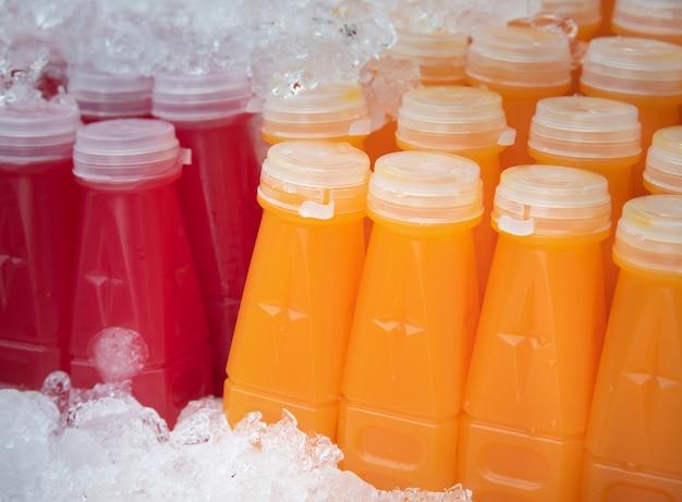 즉시 마실 수있는 플라스틱 병에 담긴 오렌지 주스와 비트 뿌리 주스.