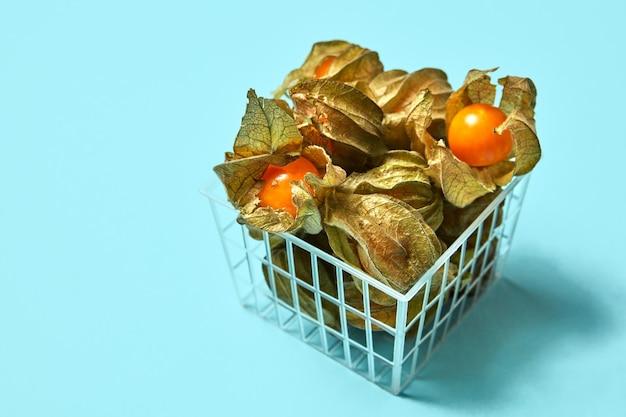 プラスチックバスケットに乾燥した葉を持つオレンジ色のジューシーなサイサリスベリー