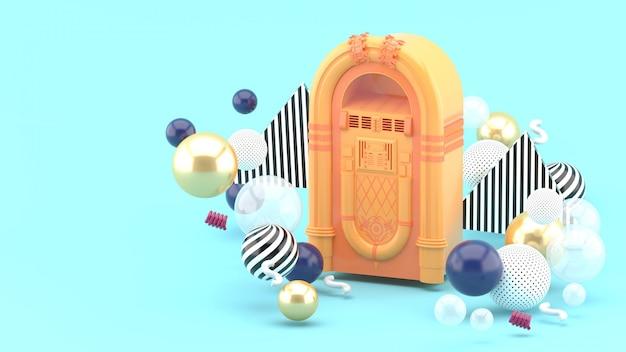 Оранжевый музыкальный автомат среди красочных шариков на сини. 3d визуализация