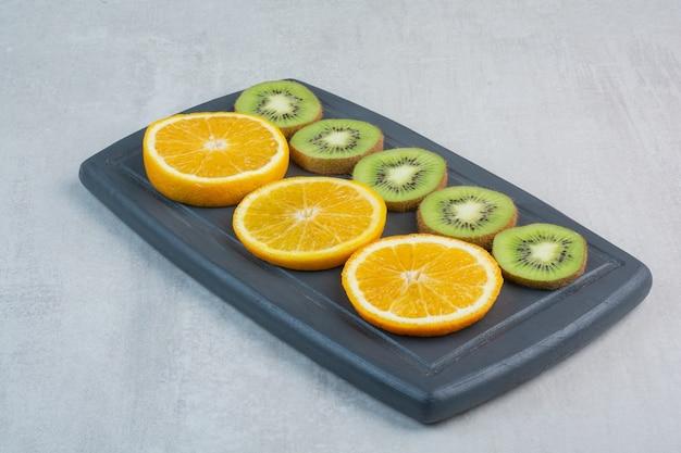 Orange and kiwi slices on dark plate