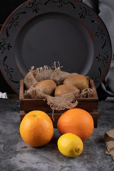 Arancia e kiwi in un fondo rustico scuro