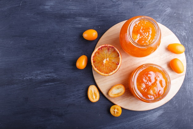 Orange and kumquat jam in a glass jar with fresh fruits on black wooden background.