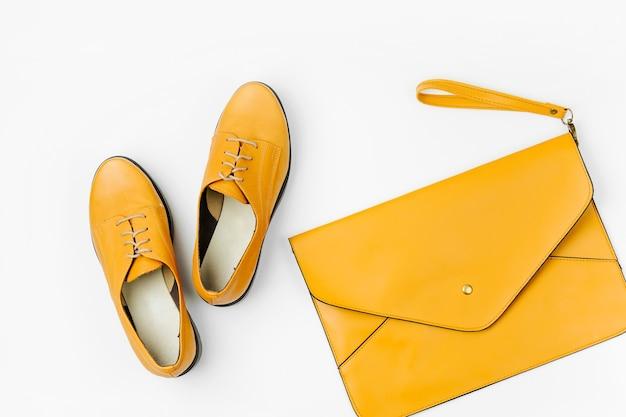 オレンジのレディースバッグとスタイリッシュな春または秋の靴。フラットレイ、上面図。最小限のファッションコンセプト