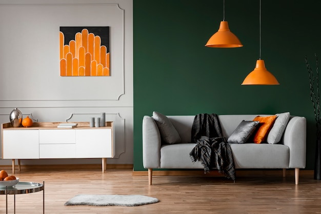 Orange lamps above grey couch in black living room interior with poster above cabinet