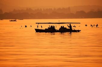 Orange landscape with fisherman on his boat