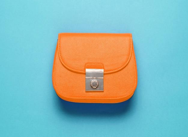 Оранжевая кожаная мини-сумка на фиолетовом фоне. концепция моды минимализм. вид сверху