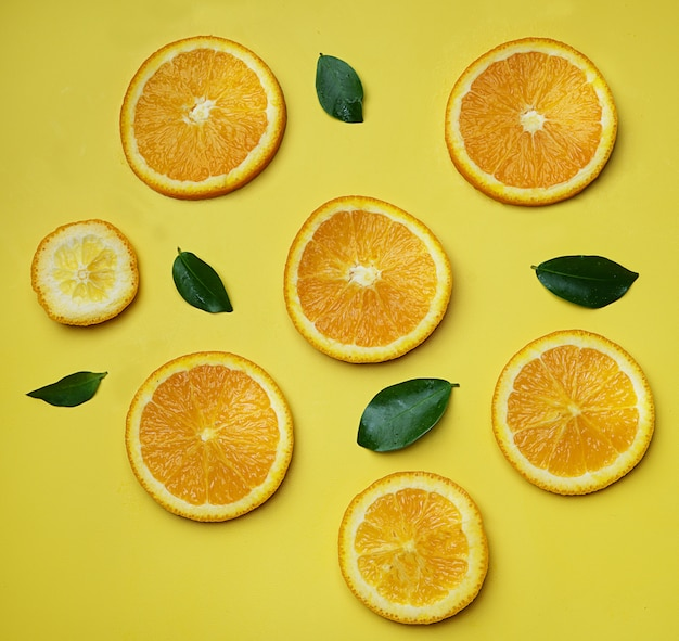 Orange leaves citrus pattern on yellow background minimal flat lay