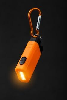 Оранжевый светодиодный фонарик с карабином на черном фоне. светодиодная подсветка в полете.