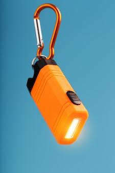 Оранжевый светодиодный фонарик с карабином на синем фоне. светодиодная подсветка в полете.