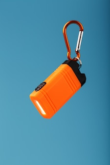 Orange led flashlight with a carabiner on a blue background. led lights in flight.