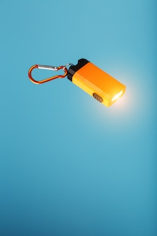 An orange led flashlight with a carabiner glows on a blue background.