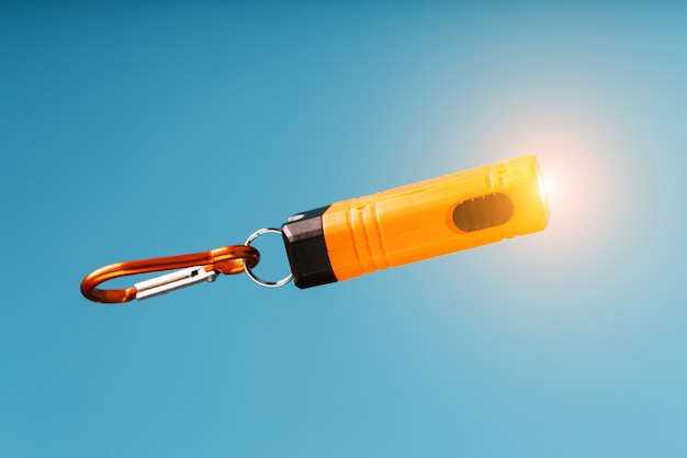 An orange led flashlight with a carabiner glows