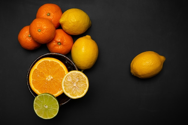 Orange and lemon are placed on a black background
