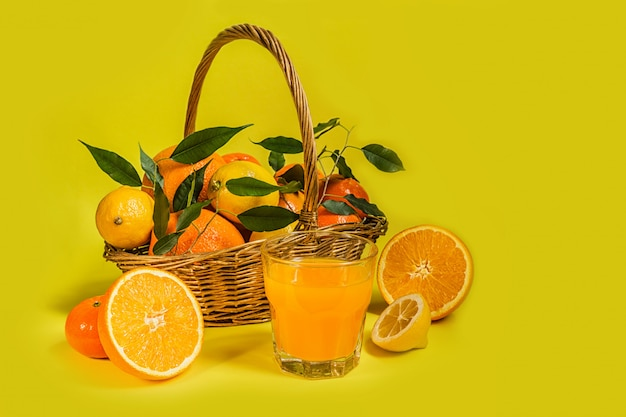 Orange lemon citrus fruit in a basket and juice on a yellow background, diet healthy food