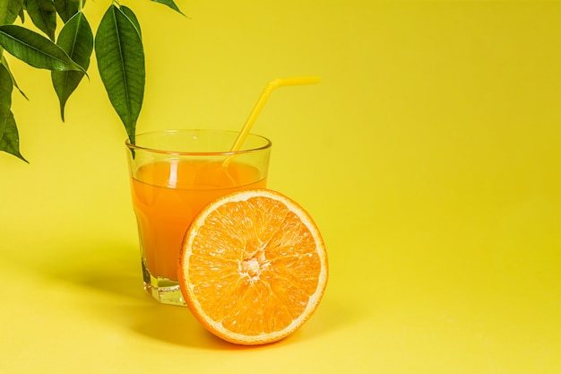 Orange lemon citrus fruit in a basket and juice on a yellow background