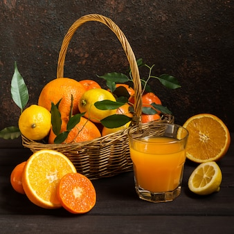 Orange lemon citrus fruits in a basket and juice on a dark background, diet healthy food