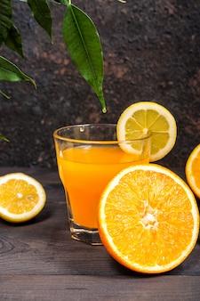 Orange lemon citrus fruits in a basket and juice on a dark background, diet healthy food