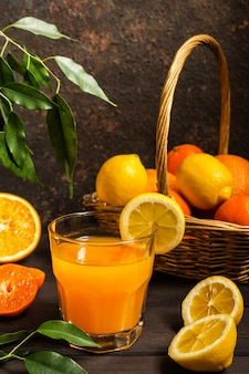 Orange lemon citrus fruits in a basket and juice on a dark background