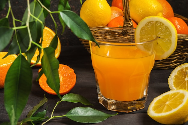 Orange lemon citrus fruits in a basket and juice on a dark background