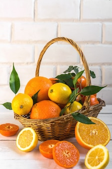 Orange lemon citrus fruits in a basket and juice on a light background, diet healthy food