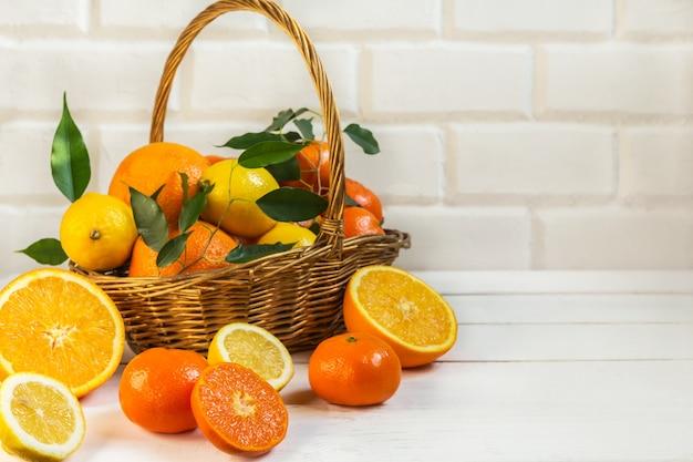 Orange lemon citrus fruits in a basket and juice on a light background, diet healthy food