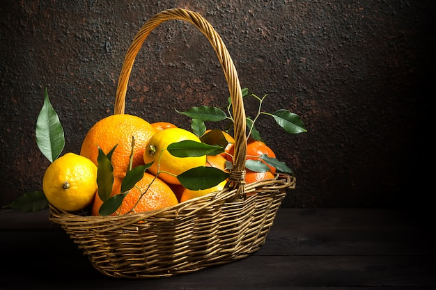 Апельсин лимон цитрусовые в корзине и сок на темном фоне, диета здоровое питание