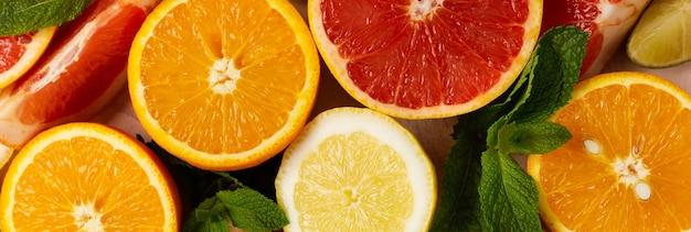トレンディなピンクの石またはコンクリートのテーブルの背景にオレンジ、レモン、グレープフルーツ、マンダリン、ライム。シトラスフルーツ。上面図、フラットレイ